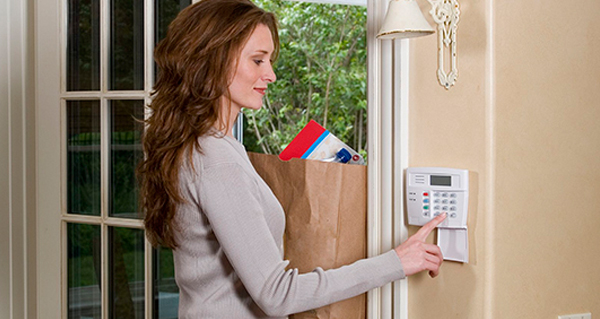 Woman pushing security alarm system